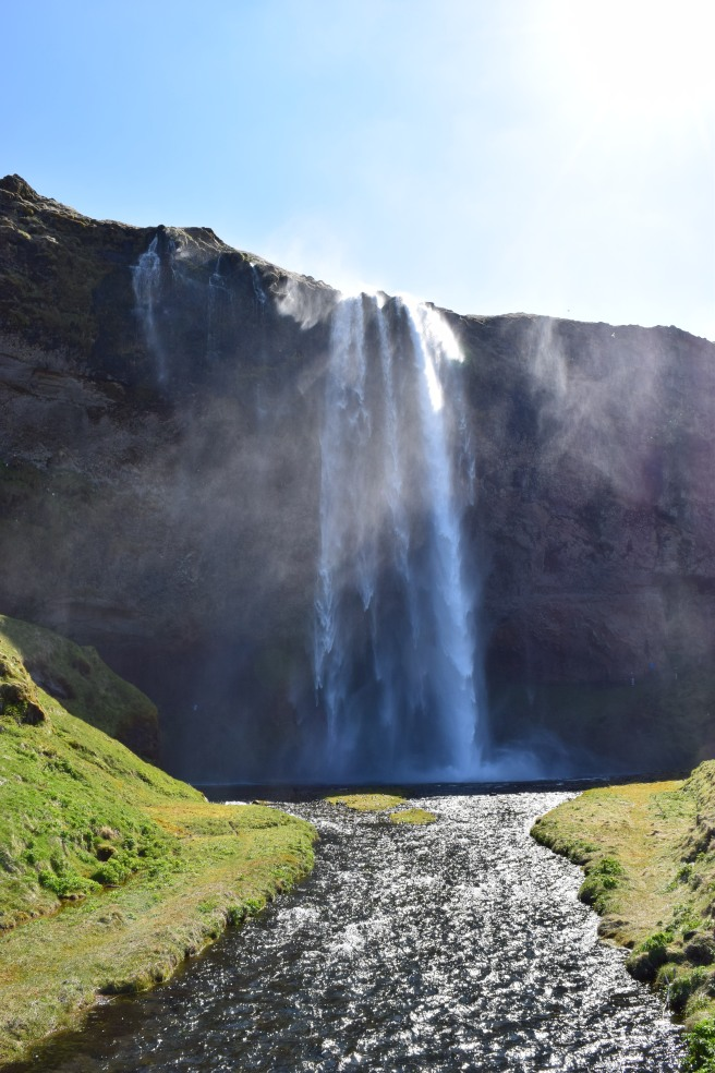 Looking towards the Seljalandsfoss Waterfall in Southeast Iceland with river running from the waterfall