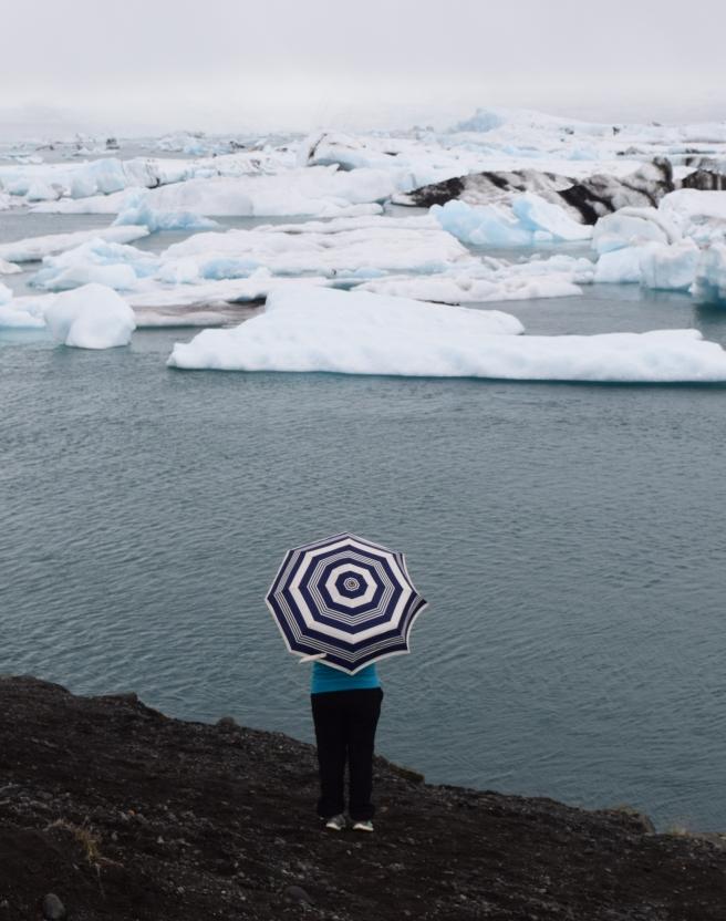 Jökulsárlón Lagoon and woman standing with umbrella on the shore