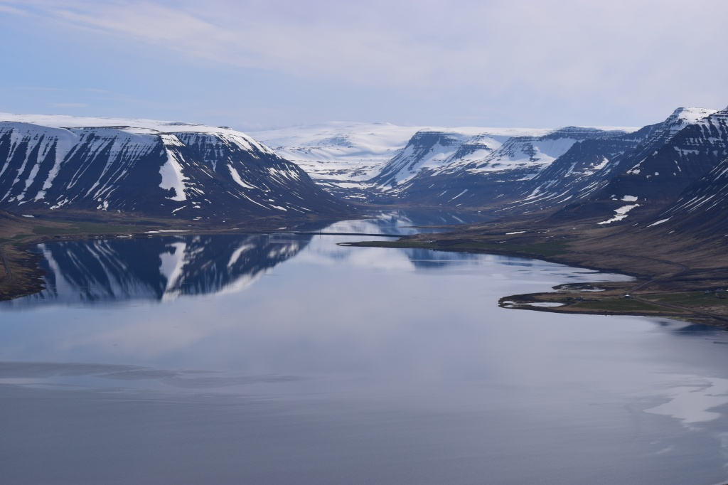 Scenery in Iceland of mountains reflecting in a nearby body of water