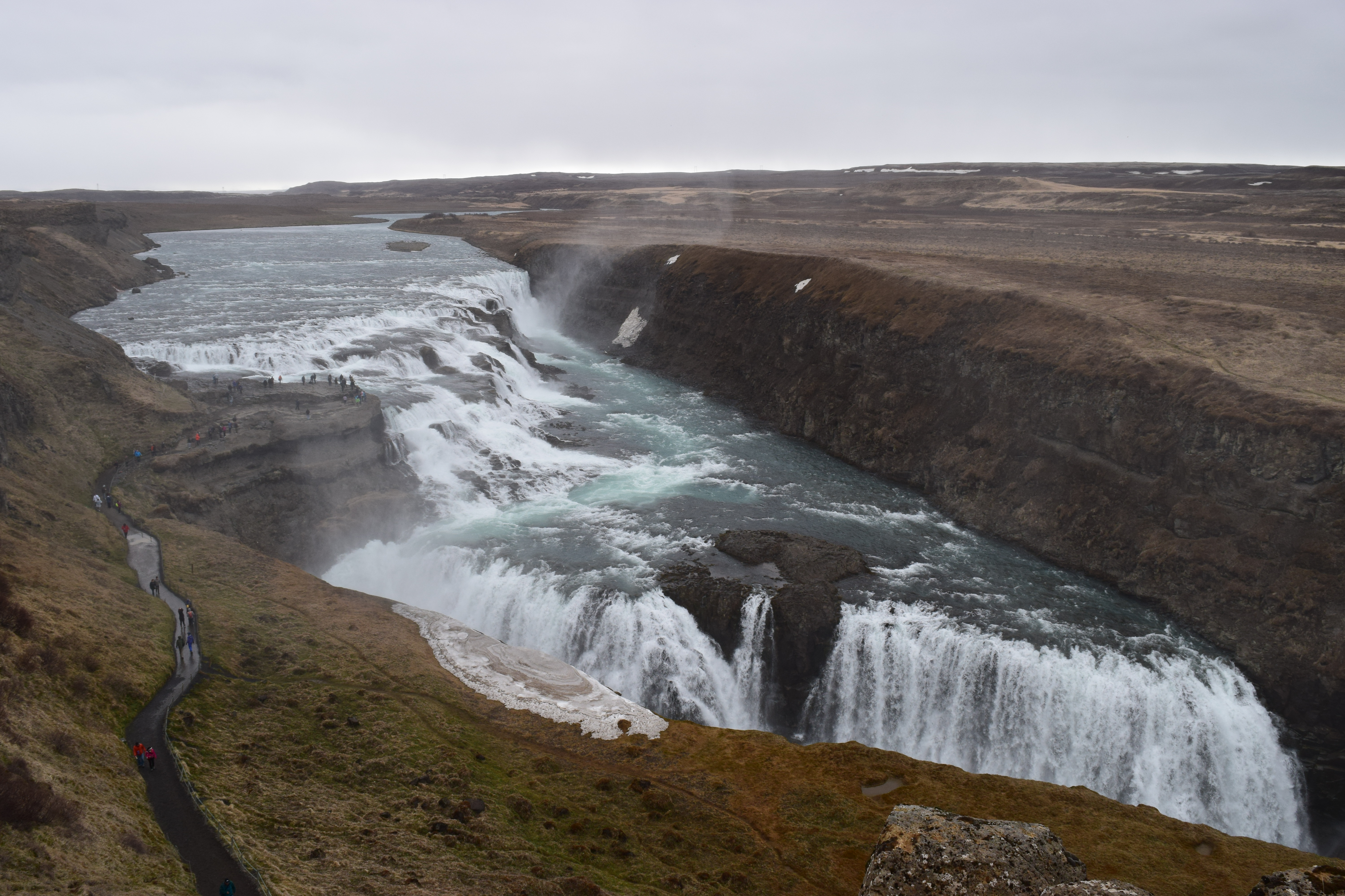 Gullfoss Waterfall in the Golden Circle from the higher lookout with a trail of people leading to the lower lookout