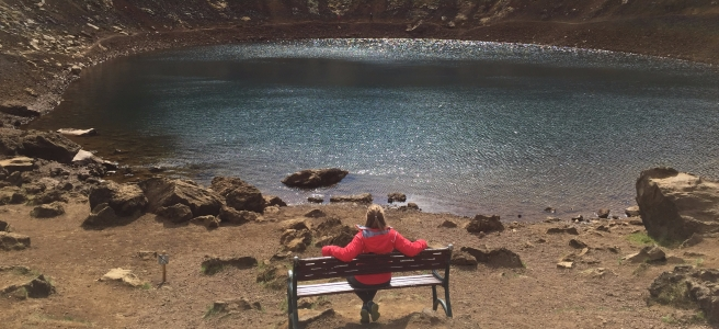 Kerid crater from the bottom trail with a woman in a pink jacket sitting on a bench
