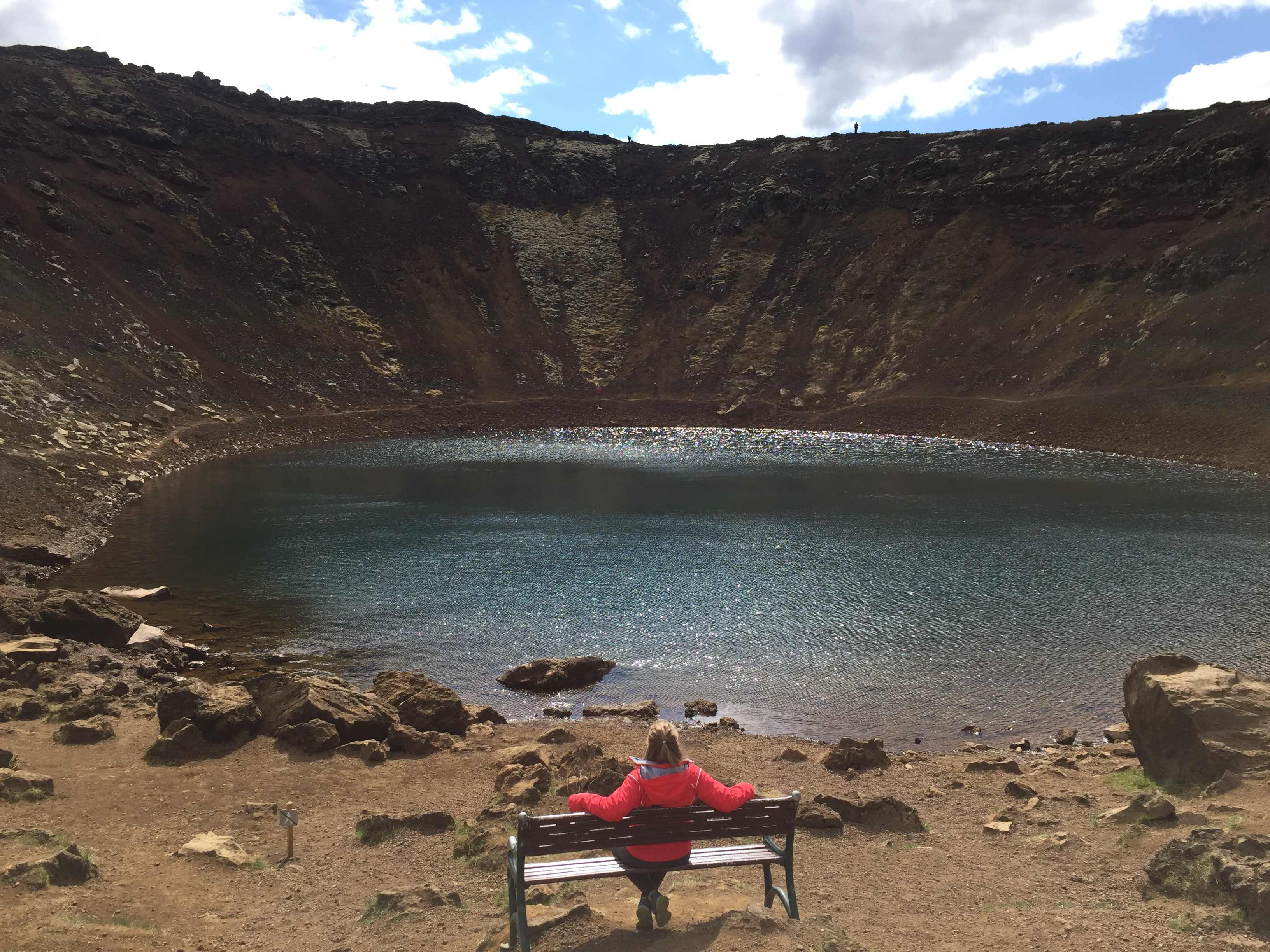 Woman in pink jacket sitting on bench in front of Kerid Crater in Iceland