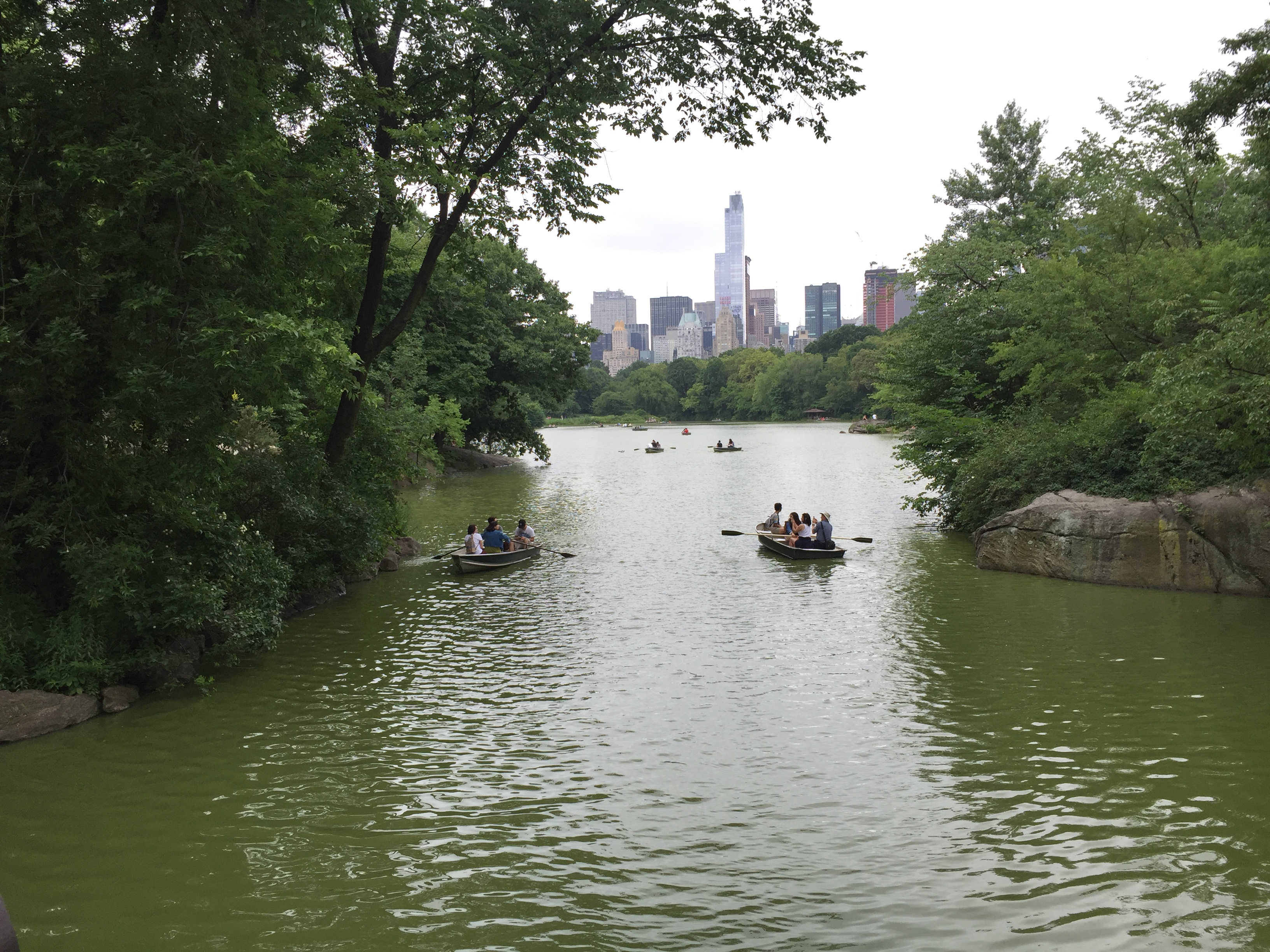 Canoeists and boaters in Central Park Lake overlooking the New York City skyline