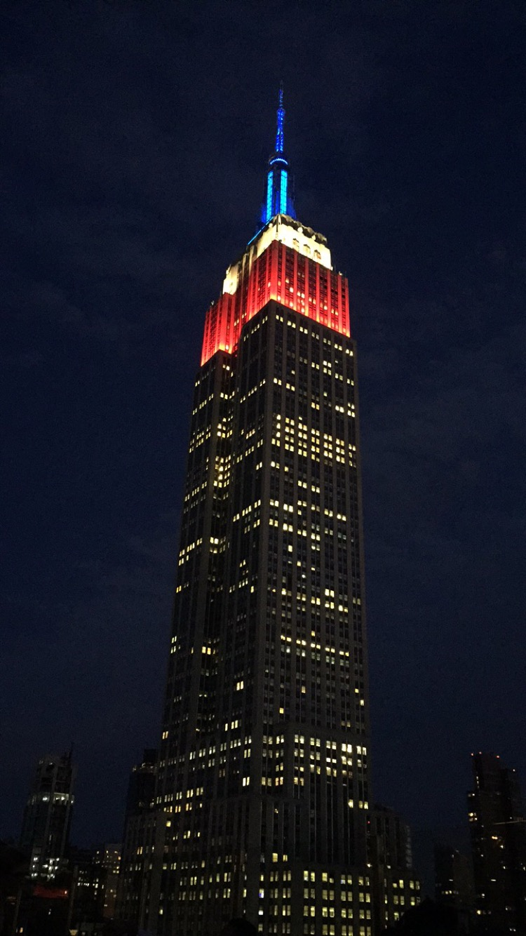 Empire State Building lit up in blue white and red seen from a rooftop bar