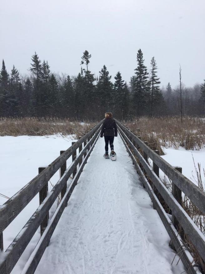 Woman in green jacket snowshoeing on a boardwalk in winter