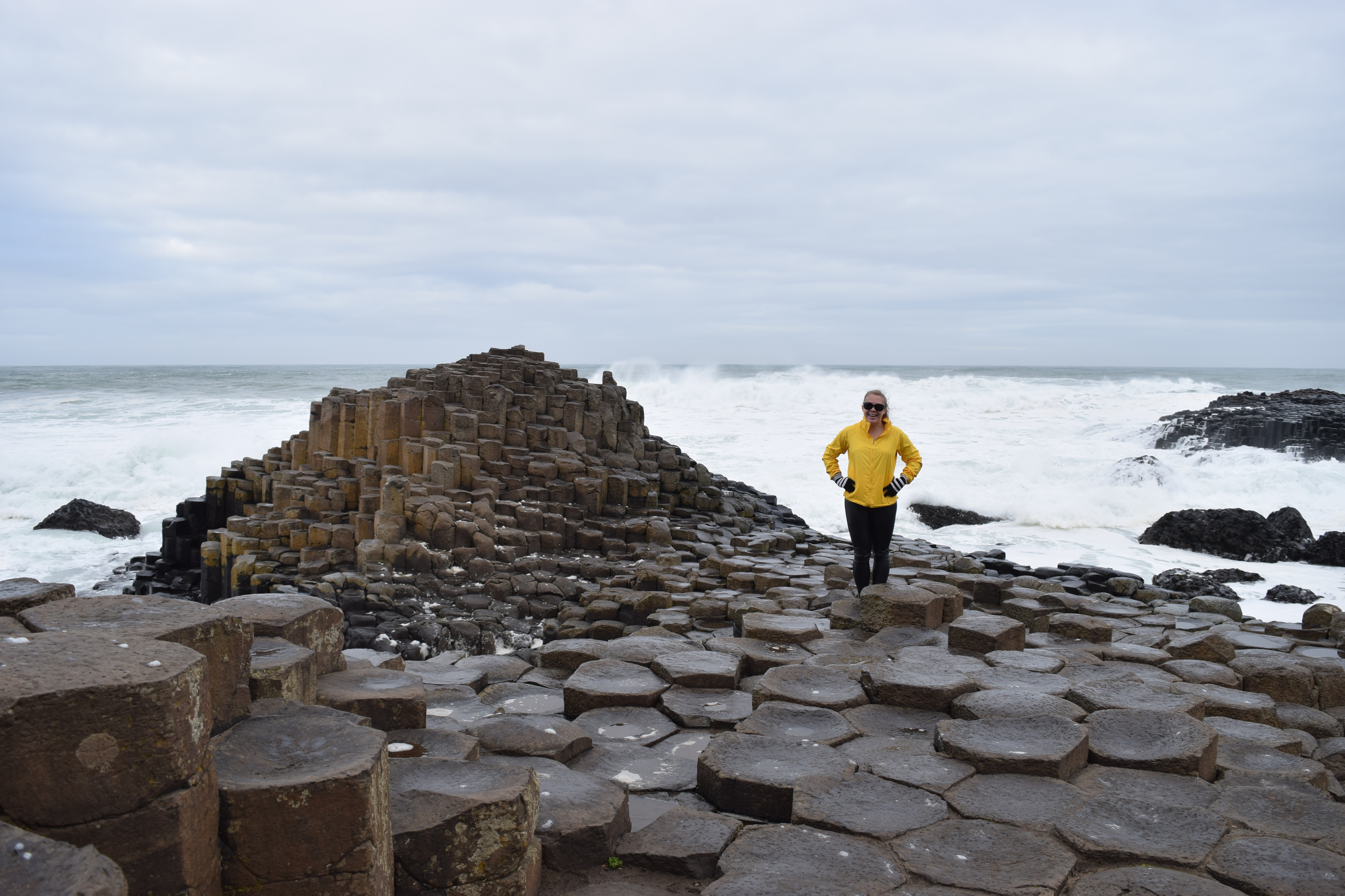 Woman in yellow jacket standing on the Giant's Causeway basalt columns in Northern Ireland