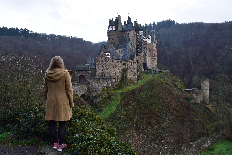 Woman in tan wool coat standing in front of the Burg Eltz Castle in Germany