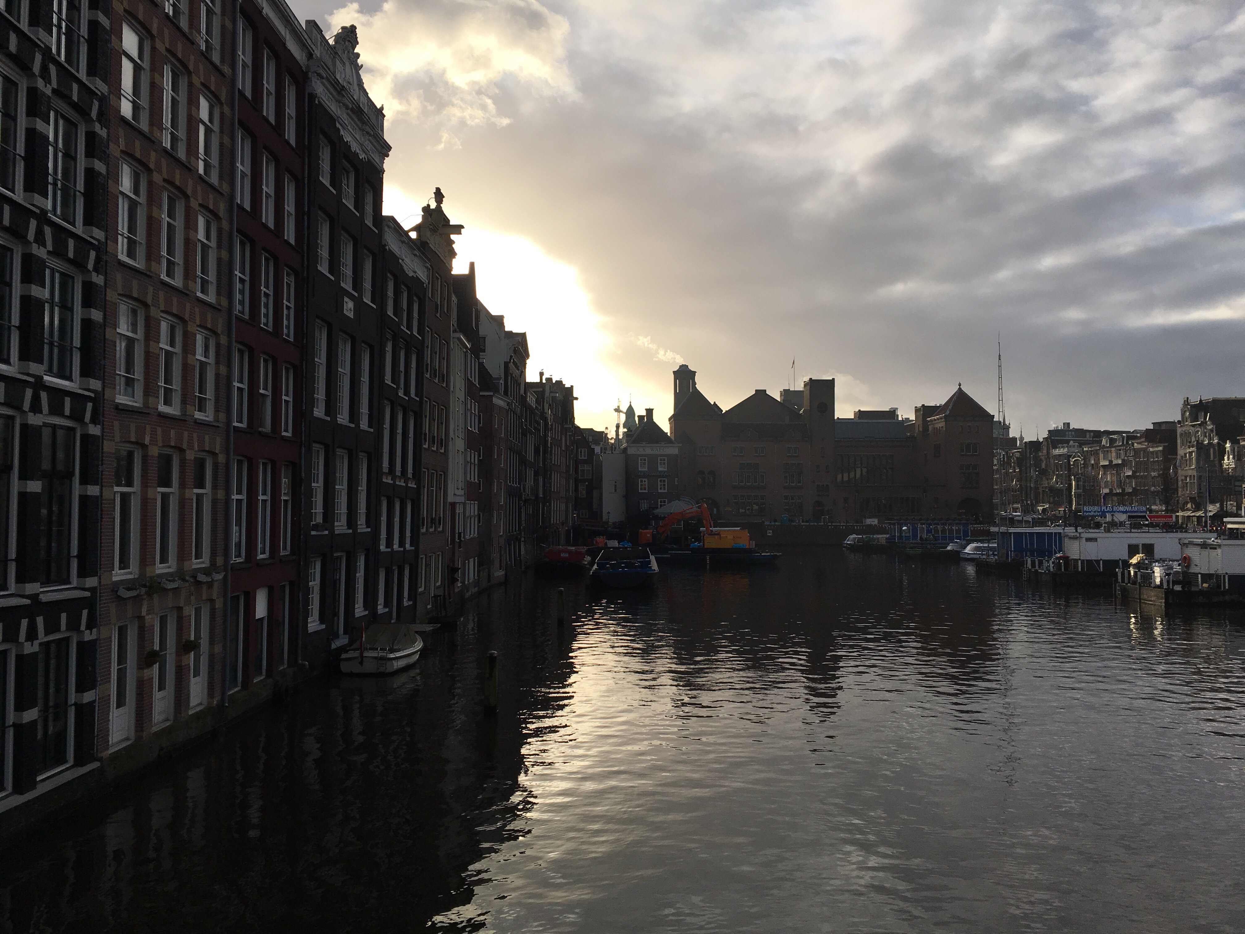 Amsterdam canal with row of houses on the left and the sun setting behind houses in the middle
