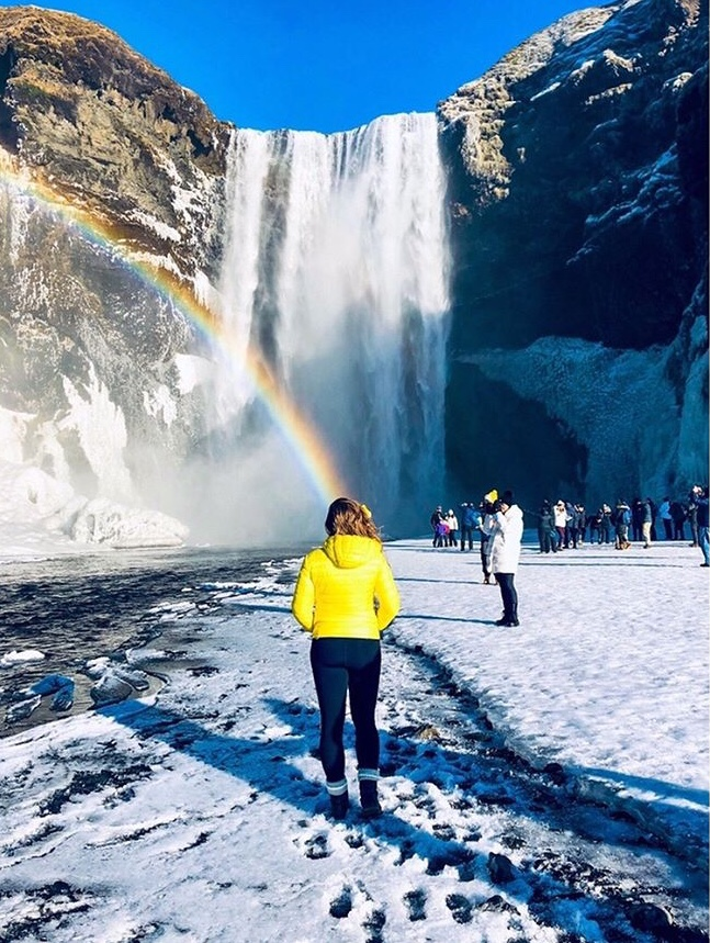 Skogafoss Waterfall with a rainbow and woman in yellow jacket in Iceland