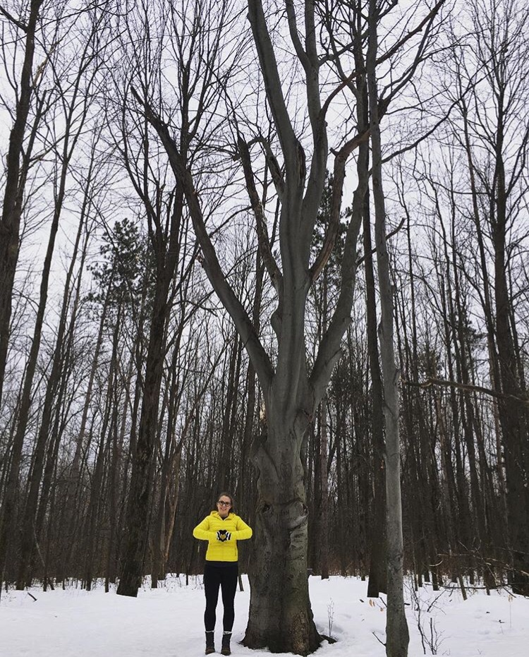 Woman in yellow jacket posing hands in the shape of a heart standing by a tree in winter