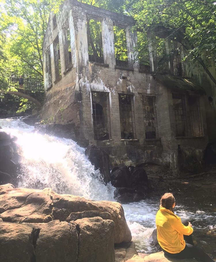 Woman in yellow jacket sitting on a rock by a waterfall and ruins