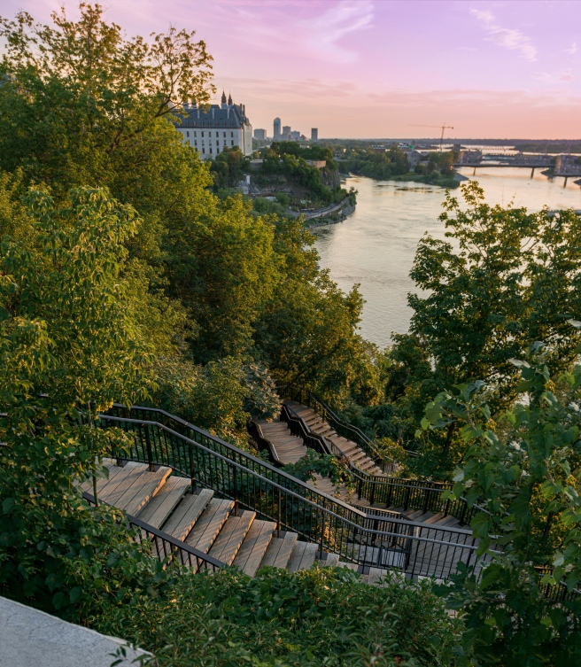 Ottawa parliament hill staircase leading down to the Ottawa River with a purple and orange sunset