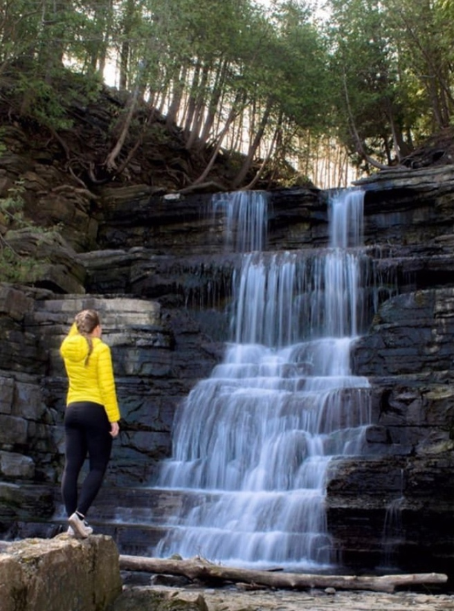 Woman in yellow jacket in front of waterfall in Orleans Ottawa Ontario Princess Louise Falls