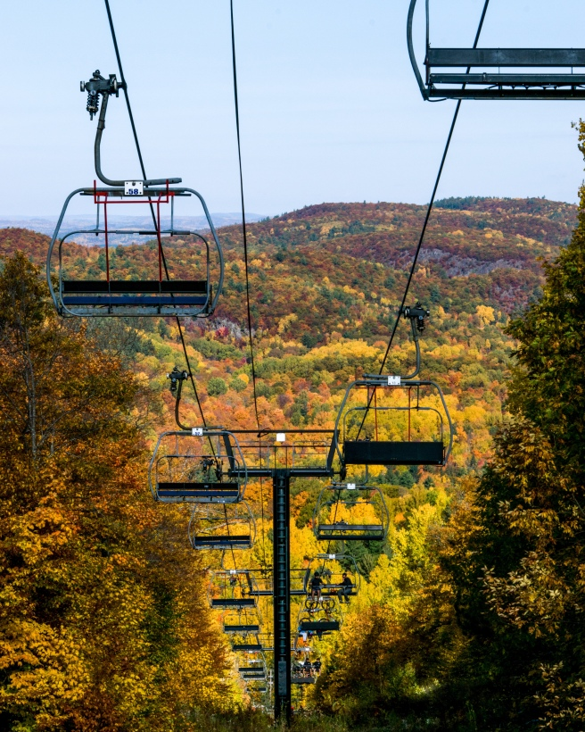 Mont Ste. Marie chairlift in the fall with a background of yellow and orange and red and green trees