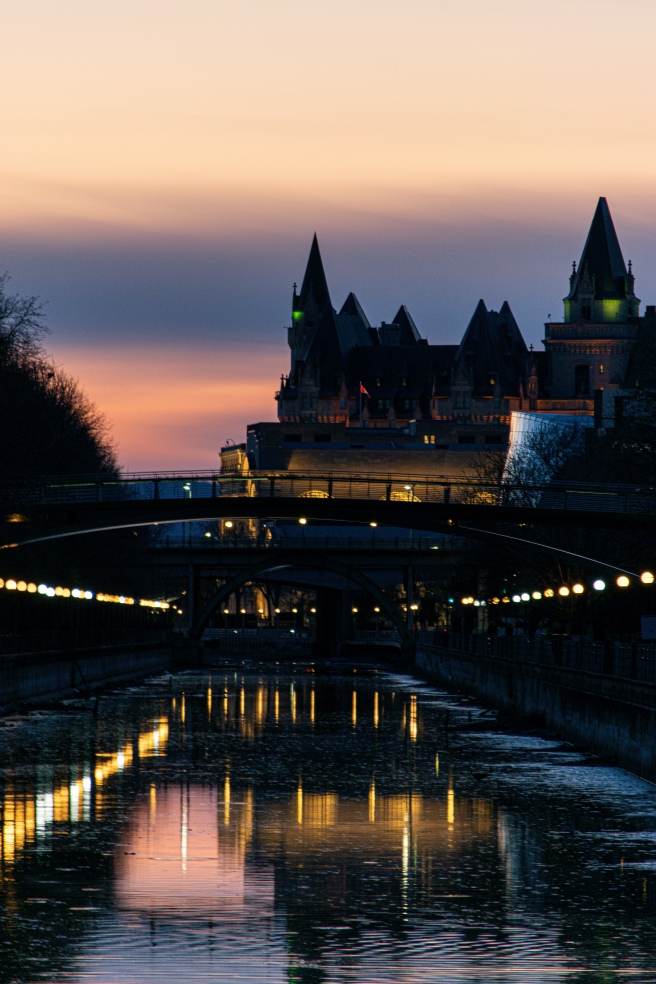 View of Chateau Laurier from a bridge looking over the Rideau Canal during a purple sunset