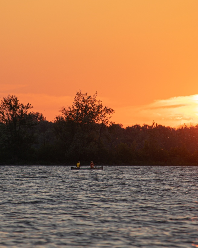 Canoeists in the Ottawa River at Shirley's Bay during an orange sunset