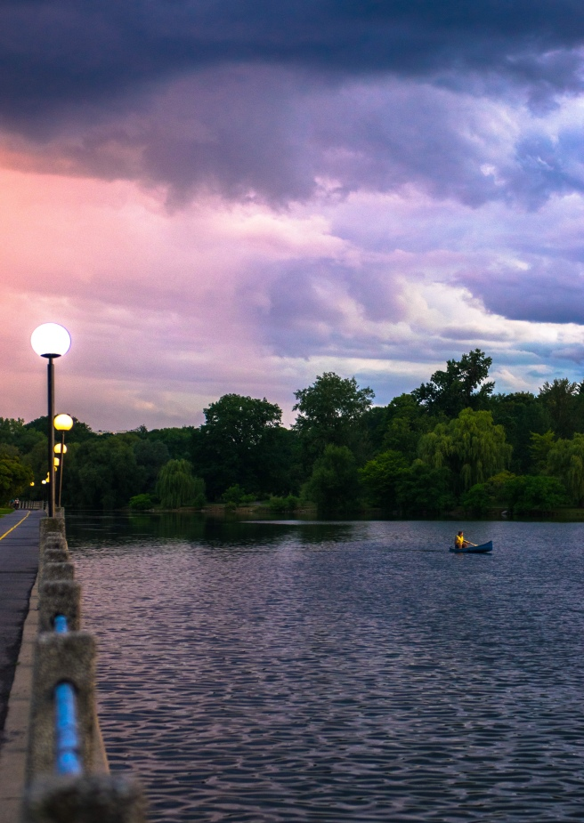 Stormy sunset on Dow's Lake with a canoeist in the lake