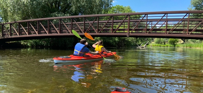 Two people in kayak on Ottawa River going under pedestrian bridge