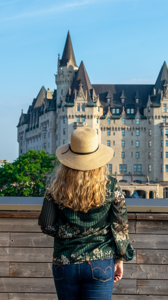 Woman in green blouse and straw hat standing in front of the Fairmont Chateau Laurier