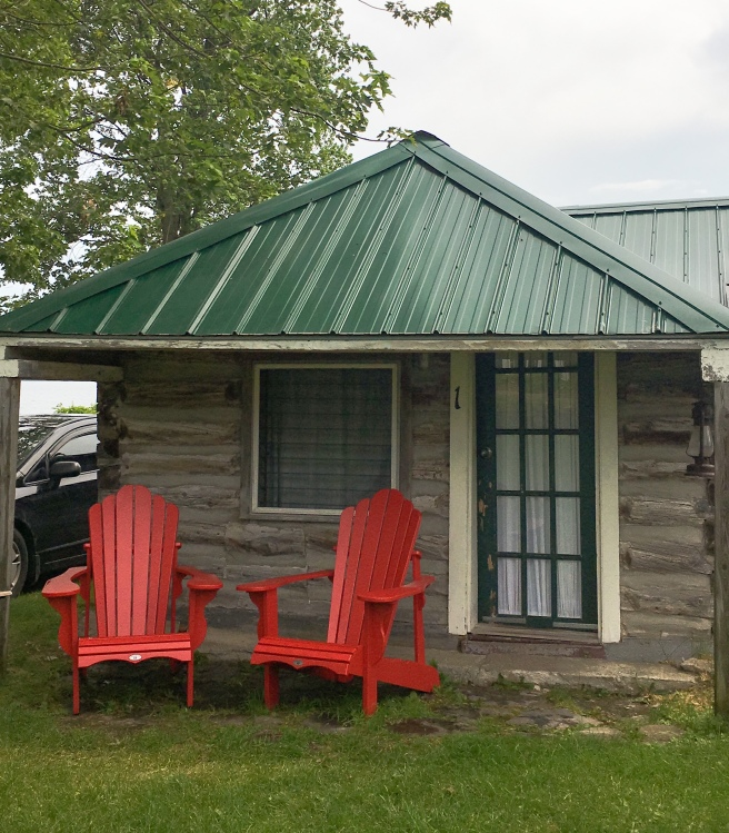 Small historic cottage with two red Adirondack chairs in Prince Edward County