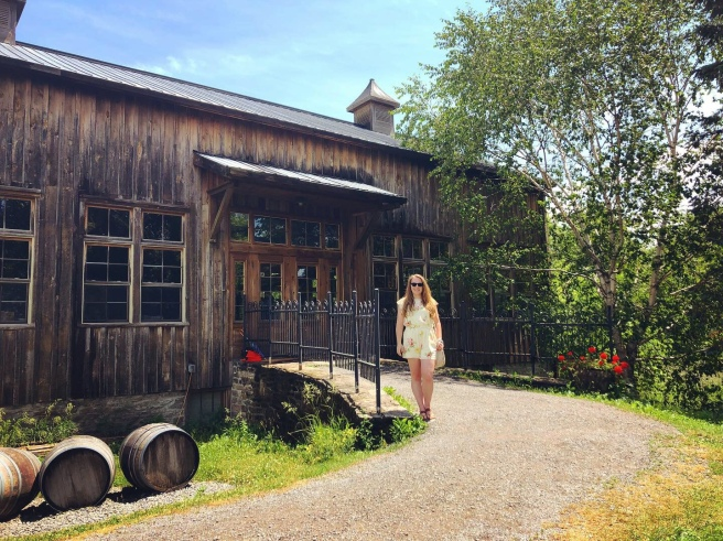 Woman in yellow romper standing in front of a wood building winery in Prince Edward County