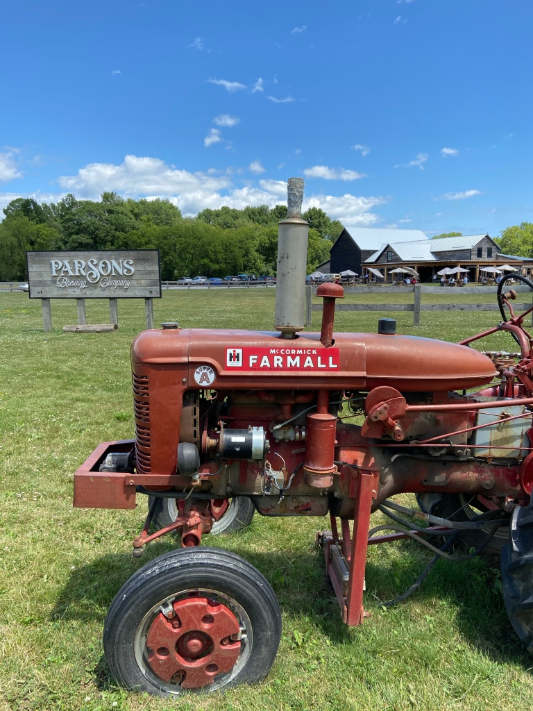 Old red tractor in front of sign for Parson's Brewery