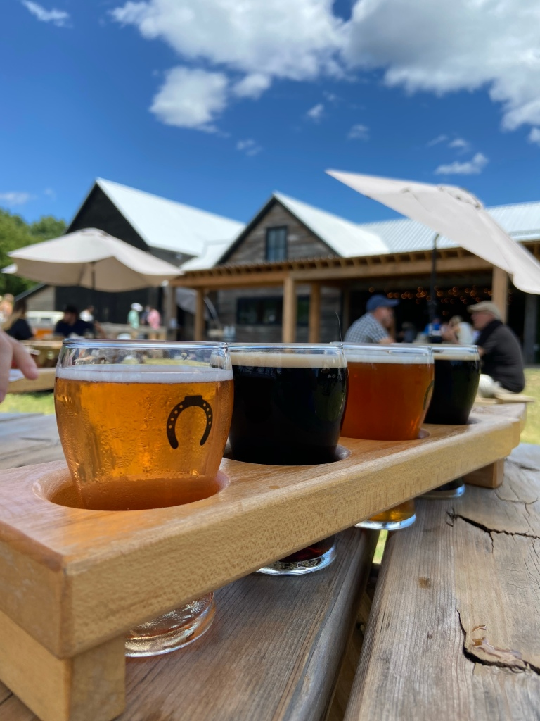 Flight of four beers on a picnic table in front of a barn at Parson's Brewing