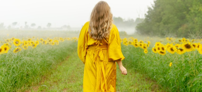Woman in yellow silk dress walking through a sunflower field