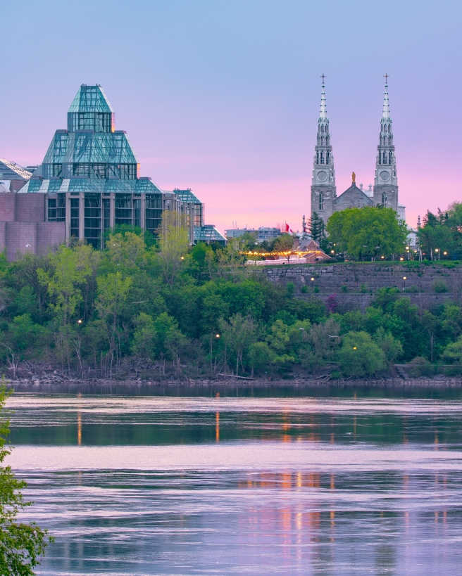 Purple and blue sunrise over the Ottawa River with the National Gallery and Notre Dame Basilica in the background