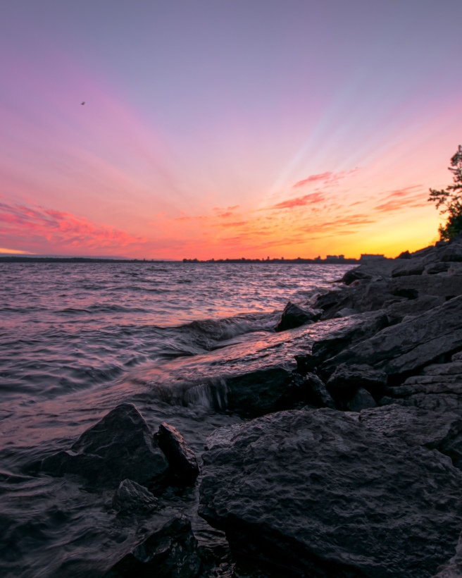 Pink and purple and yellow sunrise over the Ottawa River with a rock river bank to the right