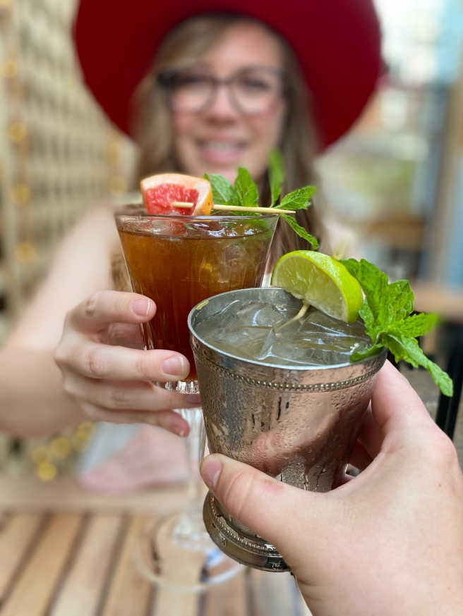 Woman smiling in a red hat cheering drinks on a patio