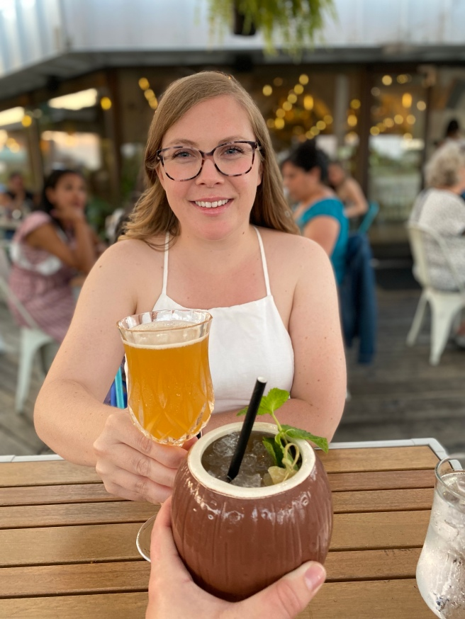 Woman in white dress cheering drinks with someone on a patio