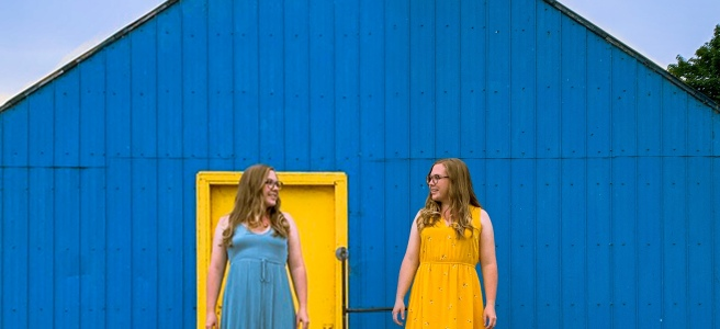 Woman in a yellow dress and a blue dress in front of a blue and yellow building