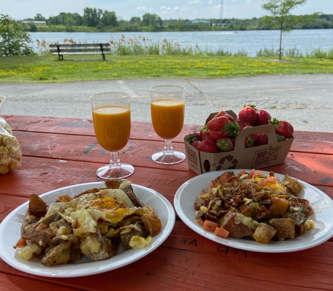 Breakfast poutine, smoothie and strawberries on a picnic table in a park