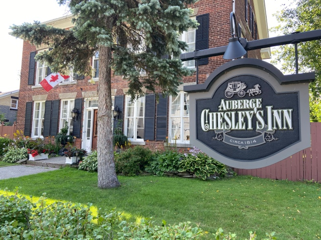 Sign hanging in front of an old brick building and a tree and canadian flag in the front yard