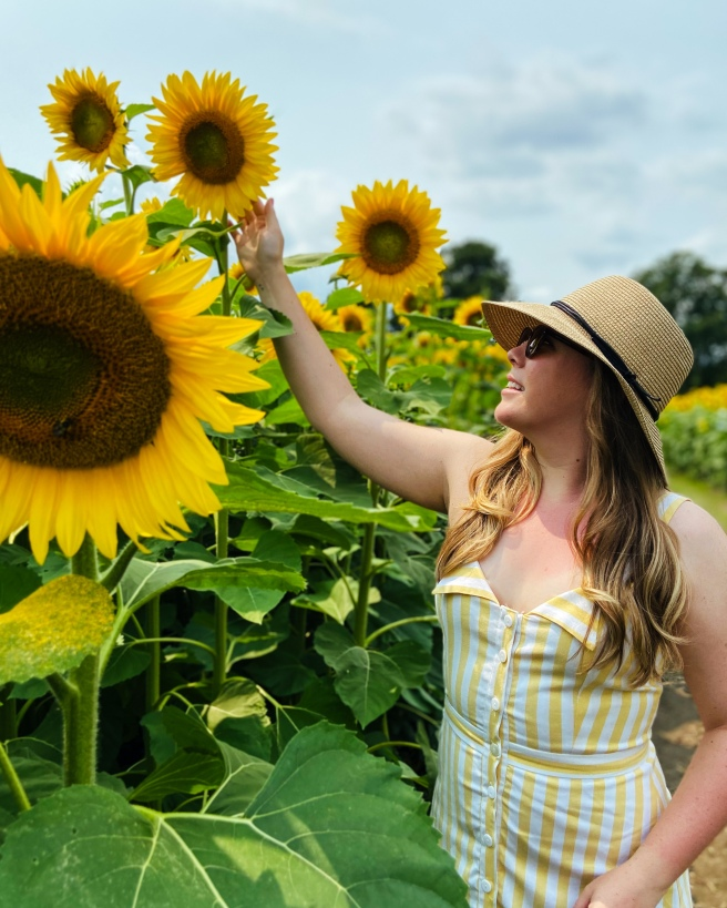 Woman in yellow and white striped dress and straw hat standing next to giant sunflowers
