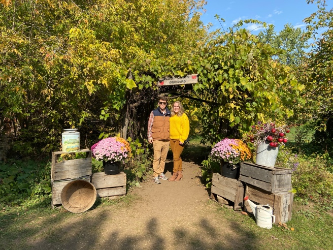 Woman and man standing in front of a sign at an apple orchard